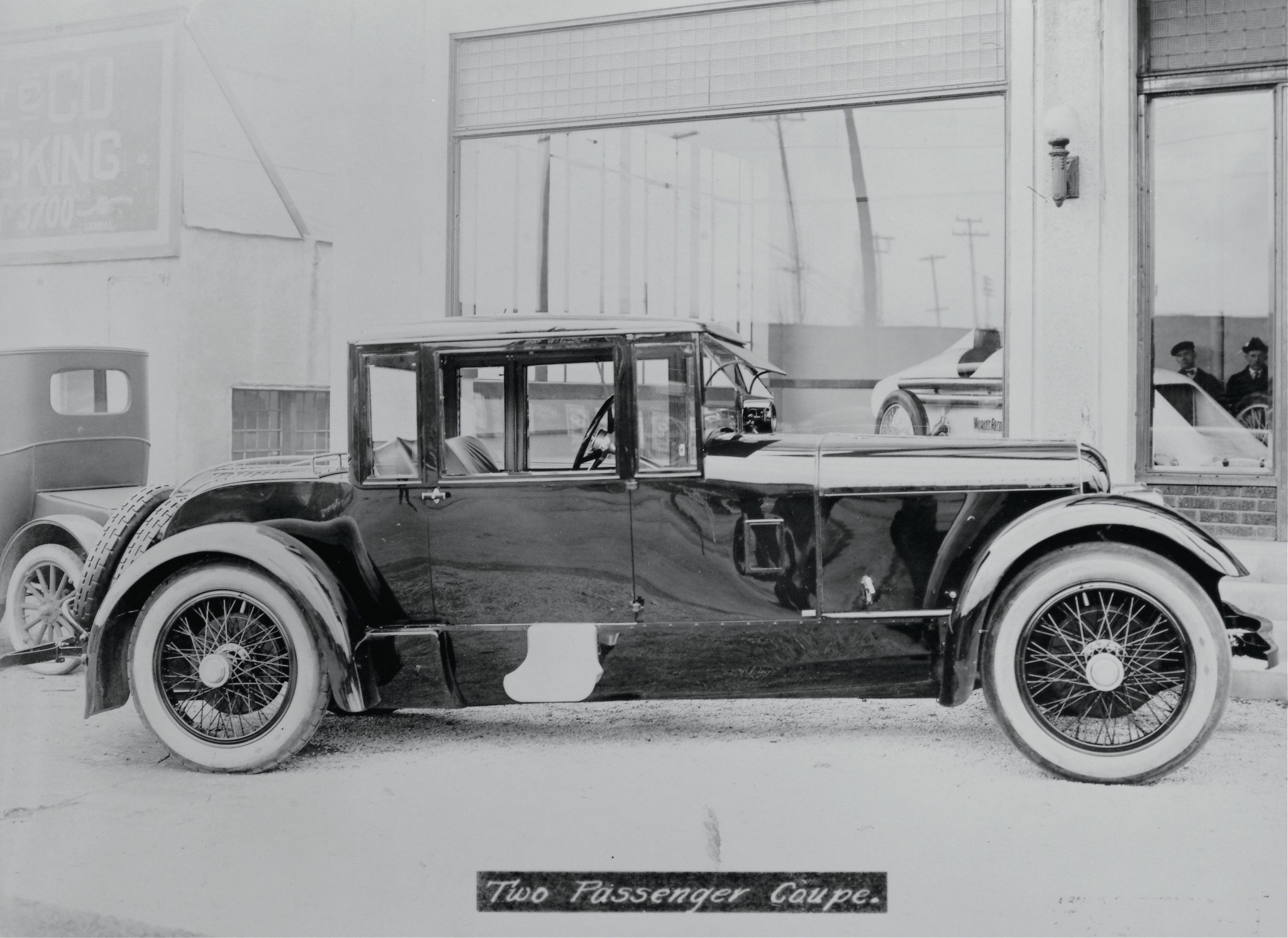 "A truly unusual body style was created by Binder for the very first Duesenberg Straight Eight built and sold in 1921. The car is pictured in front of the Indianapolis, Indiana, showroom. On the showroom floor is Tommy Milton's ""Twin 8"" record car, which hurtled to seven world speed records at Daytona Beach in 1920."