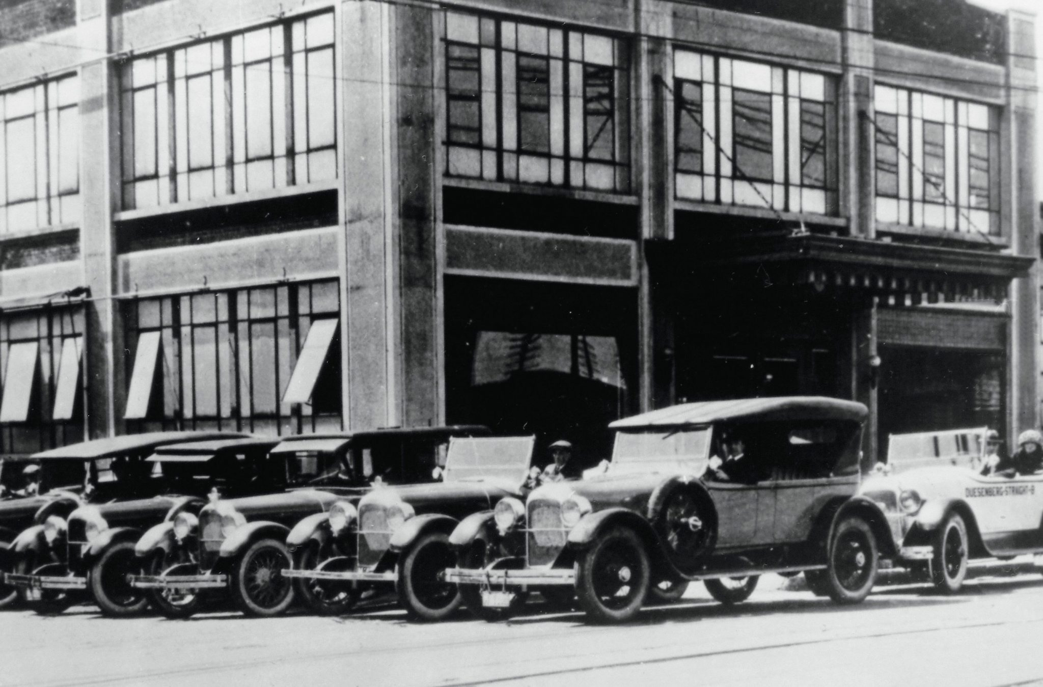 Publicity photos had become essential by 1923 when this shot was taken in front of the Duesenberg Company's main entrance on Washington and Harding Streets. Among the Model A body styles shown was the record setting phaeton (far right) that had completed three-weeks and 18,000 miles of endurance tests at the Indianapolis Motor Speedway, and then served as the pace car for the 500-mile Memorial Day classic in May.