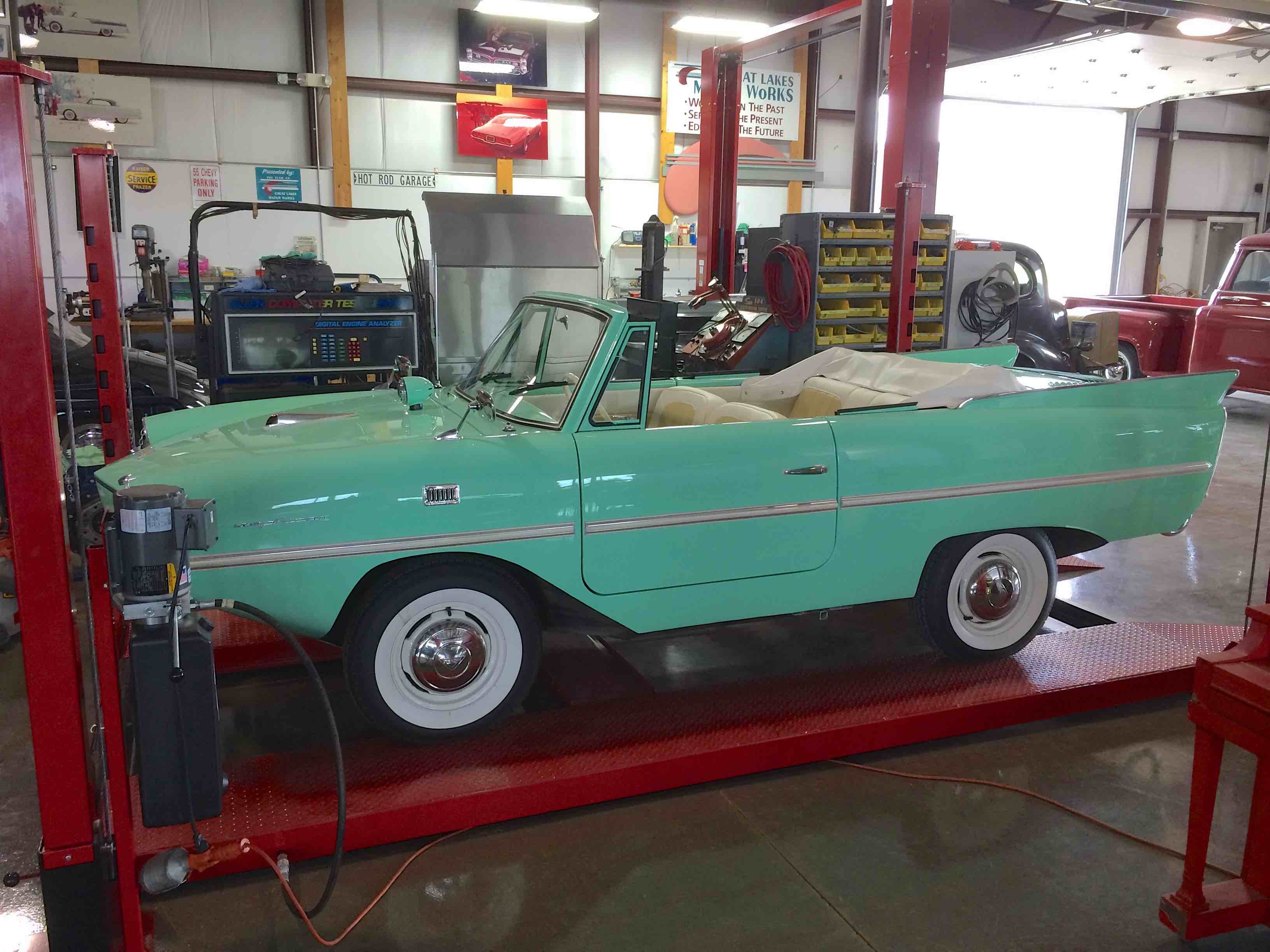 Vintage teal convertible up on a shop lift