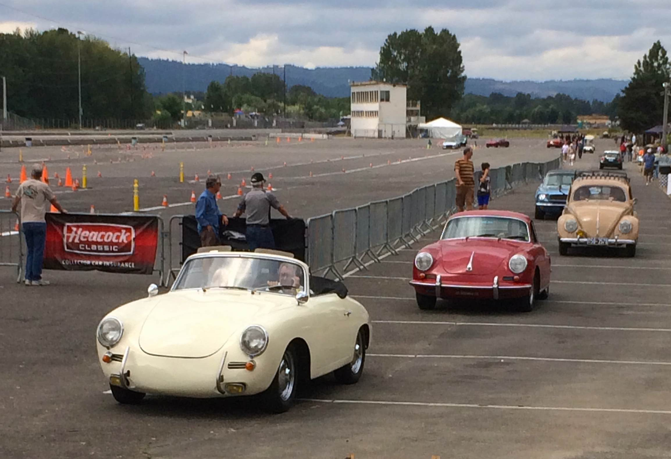 Classic Porsches and VW driving through a car show or tour parking lot